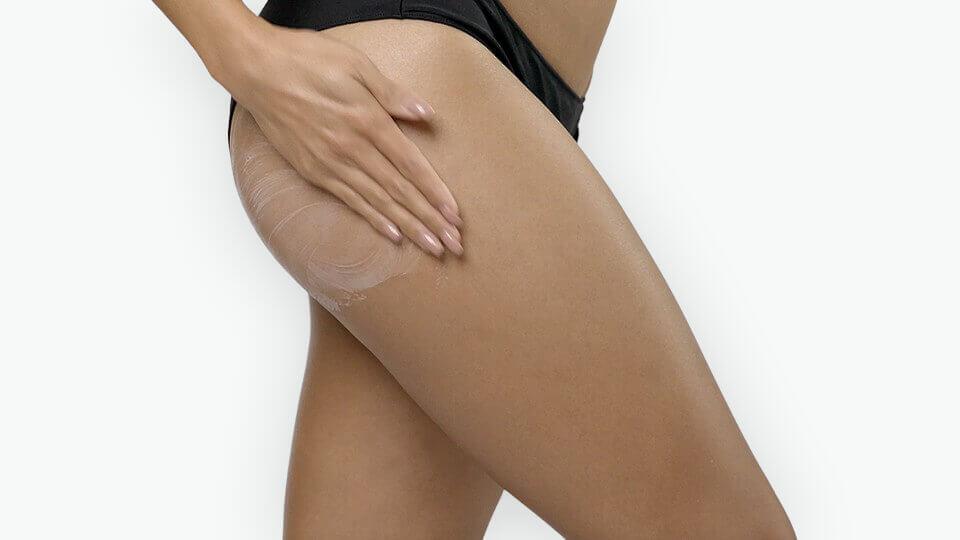 woman applying cream on buttocks